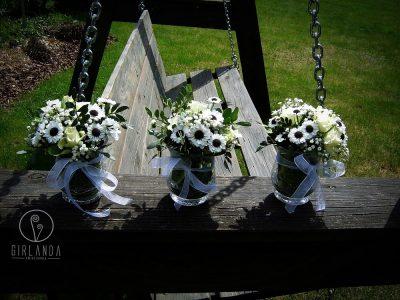 kompozycje białych kwiatów na stół w sali weselnej